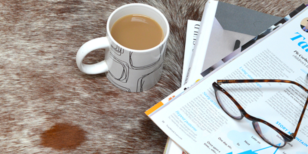 Coffee, magazines and glasses sit on top for a cow hide