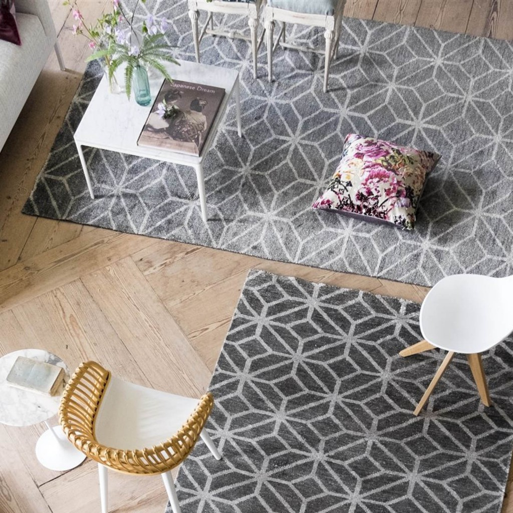 A bird's eye view of designer rug brand designers guild features two grey and white geometric rugs in a living room