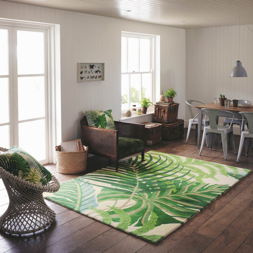 a tropical green rug lays on the floor of an open kitchen against a dark wood flooring designer rug brands Sanderson