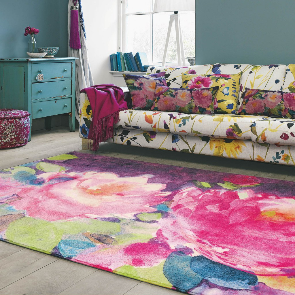 A Bright Pink, Blue And Green Floral Rug Sits In A Cottage Living Room;