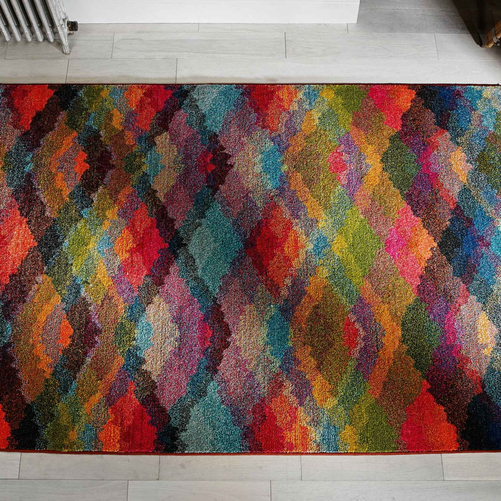 multi-coloured kaleidoscope prism rug against a white wooden floor for a prize as a pinterest competition