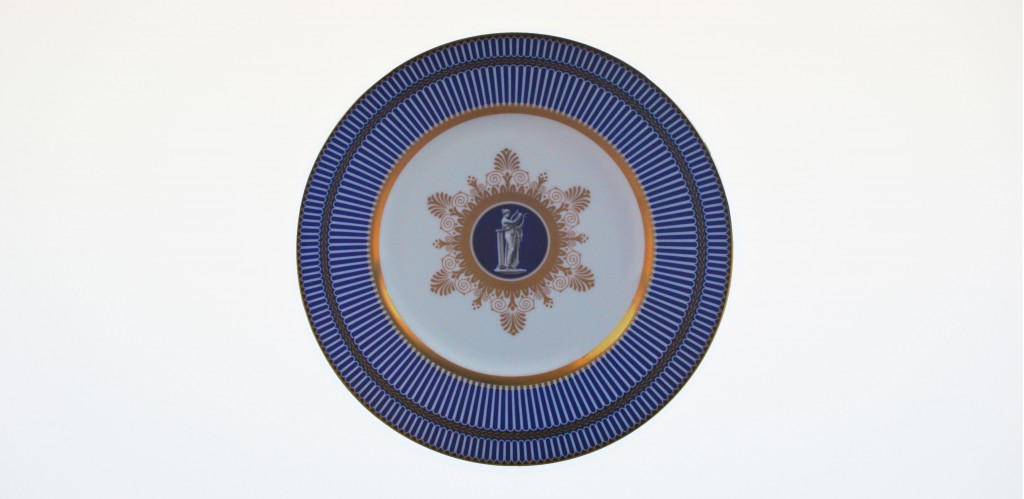 A ceramic blue, gold and white plate positioned in the center of the image, placed on a clear white wall background at world of wedgwood