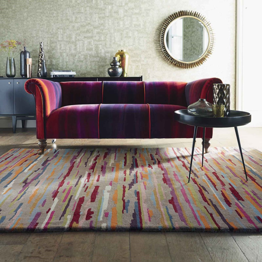 a bright purple, red and orange sofa sits underneath a multicoloured striped rug
