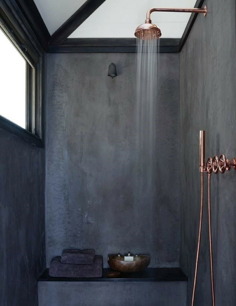 Dark concrete wetroom shower with copper interiors showerhead