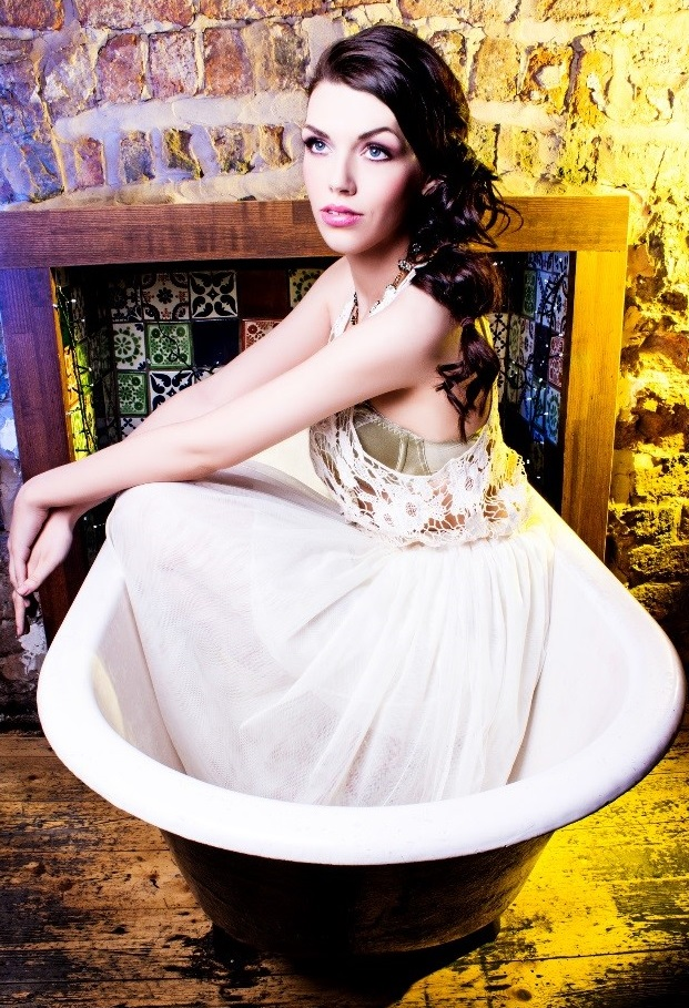 Portraiture photography shot of a glamourously dressed woman sitting elegantly in a white bathtub