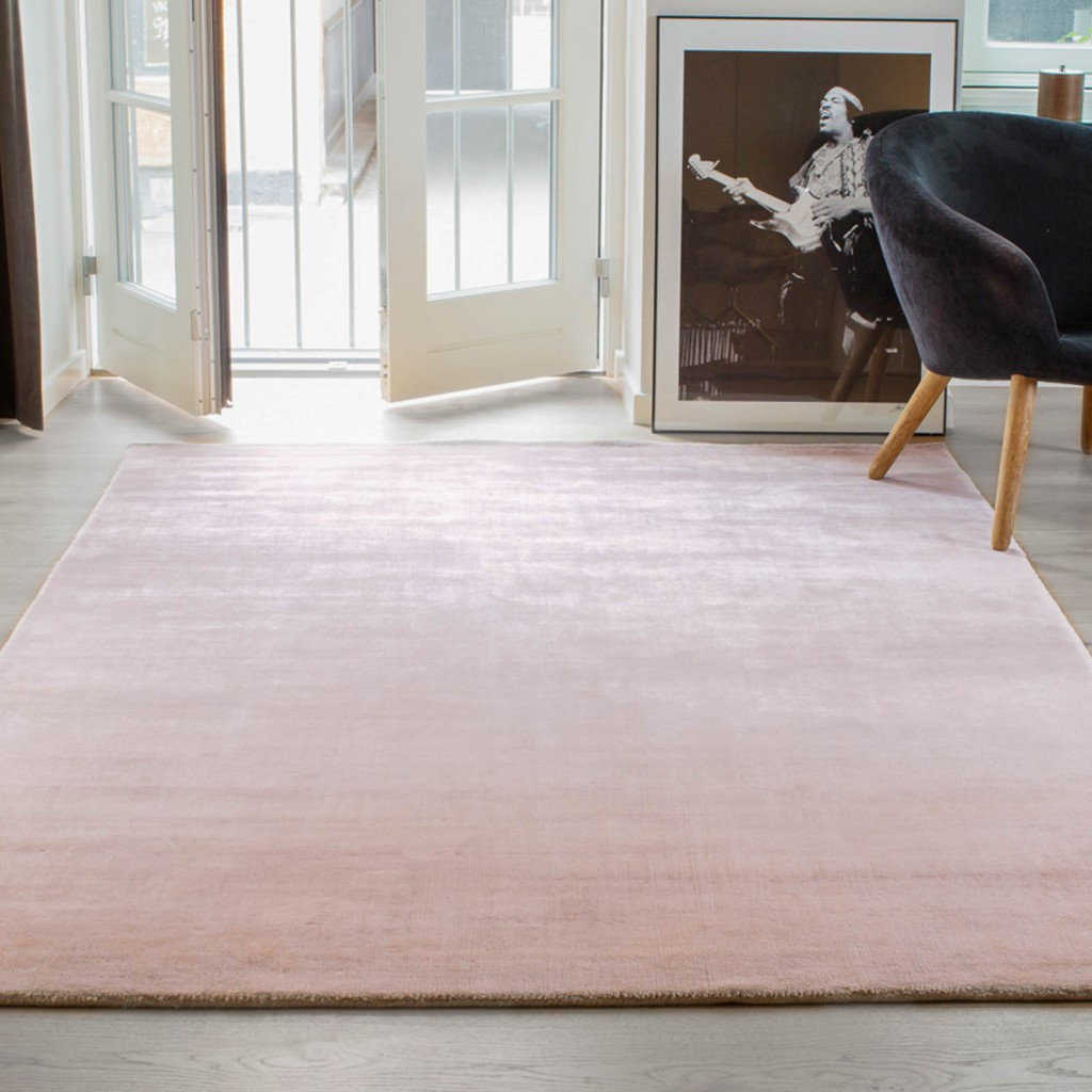 Rose pink coloured plain Massimo rug in a large space with complementing furniture accents surrounding