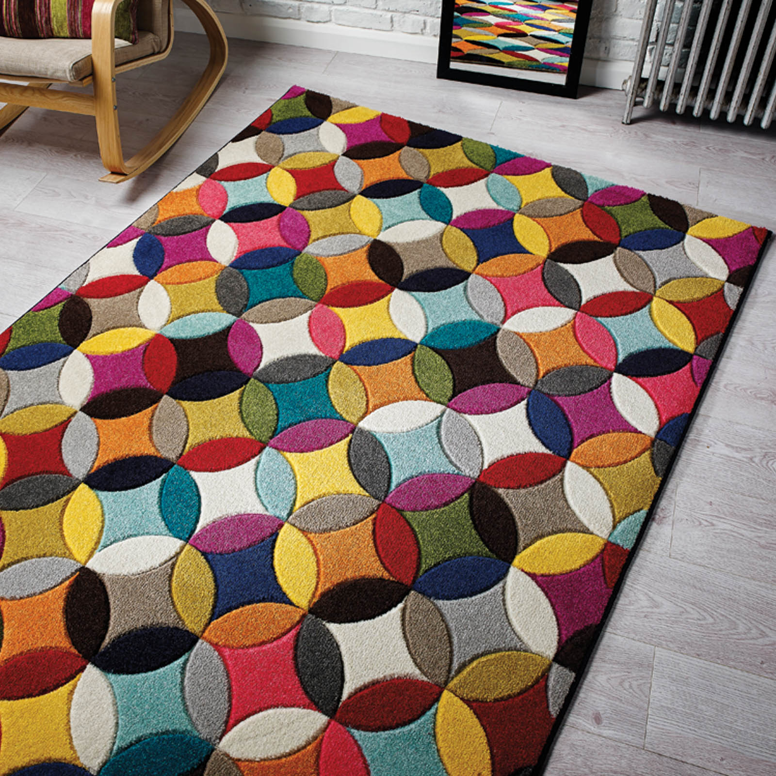 A multicoloured, circular design floor piece on a ligth grey coloured flooring