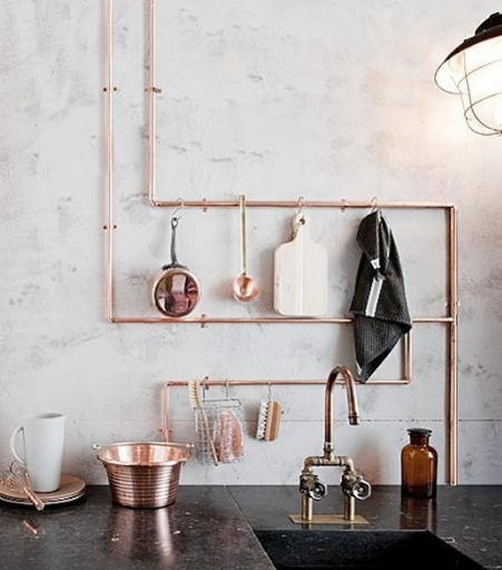 Copper Interiors With Copper Pipes And Kitchen Utensils Against A White Wall