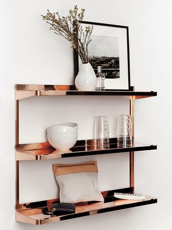 copper shelving with a variety of white accessories on a white wall for copper interiors