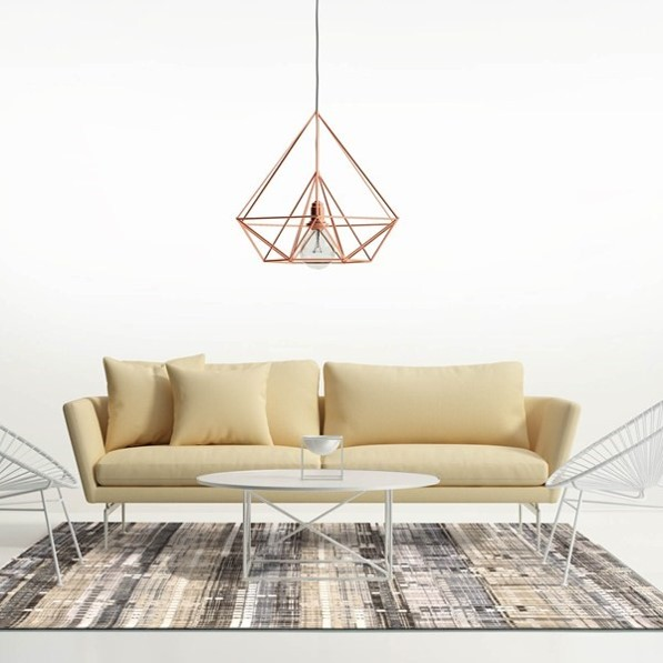 Copper interiors cage lampshade over a yellow sofa and copper thread rug in a white minimalist room