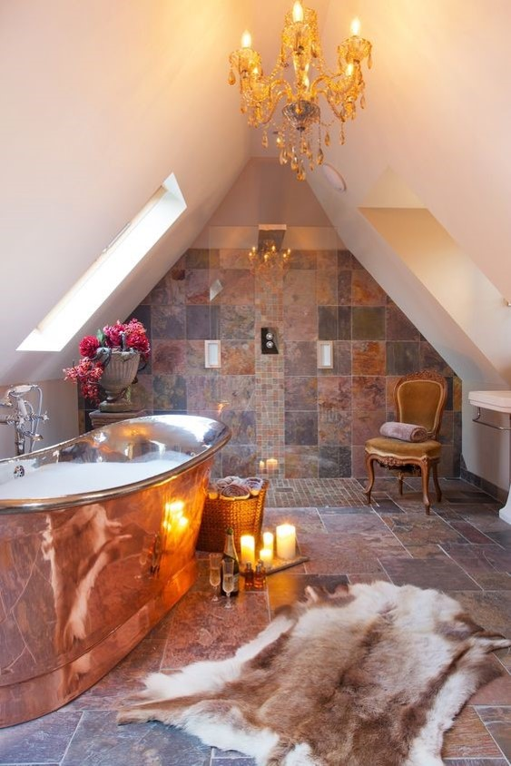 marble tiled bathroom lit with candles with a large freestanding copper bath for copper interiors