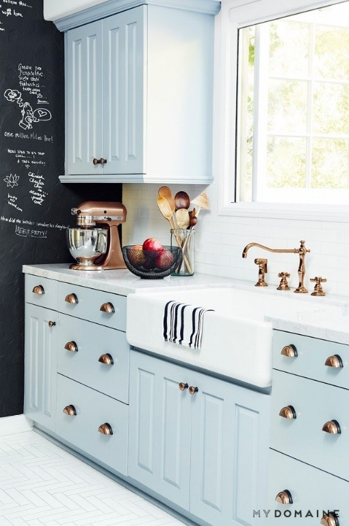 Pale kitchen interior with copper interiors handles