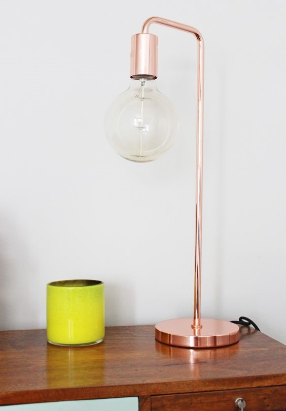 copper base lamp on a wooden desk against a white wall for copper interiors