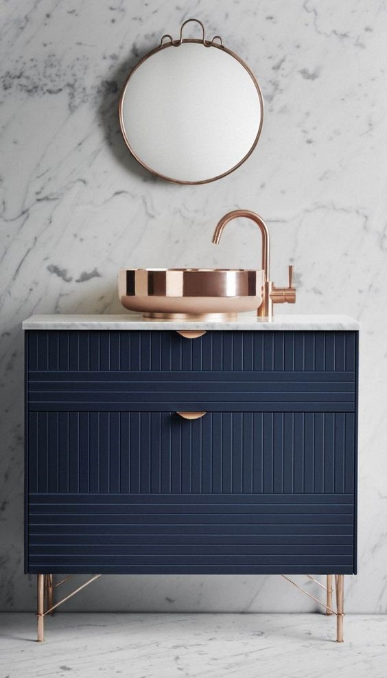 Marble style wall and dark blue bathroom cabinet with copper feet, handles and mirror for copper interiors