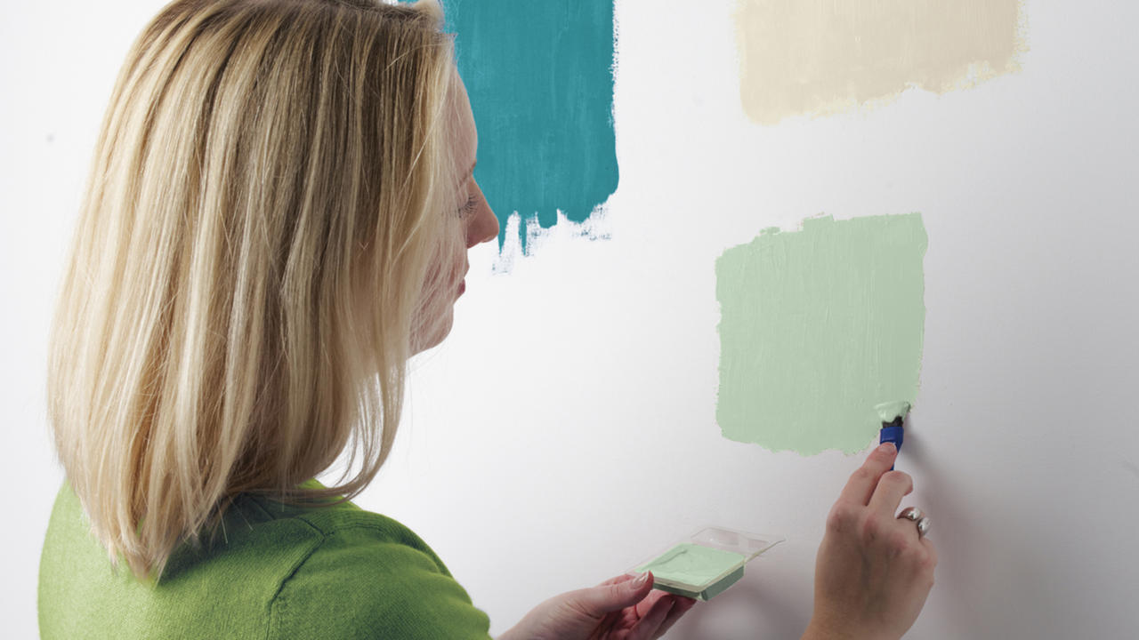 how to paint a room a woman testing paint on a white wall