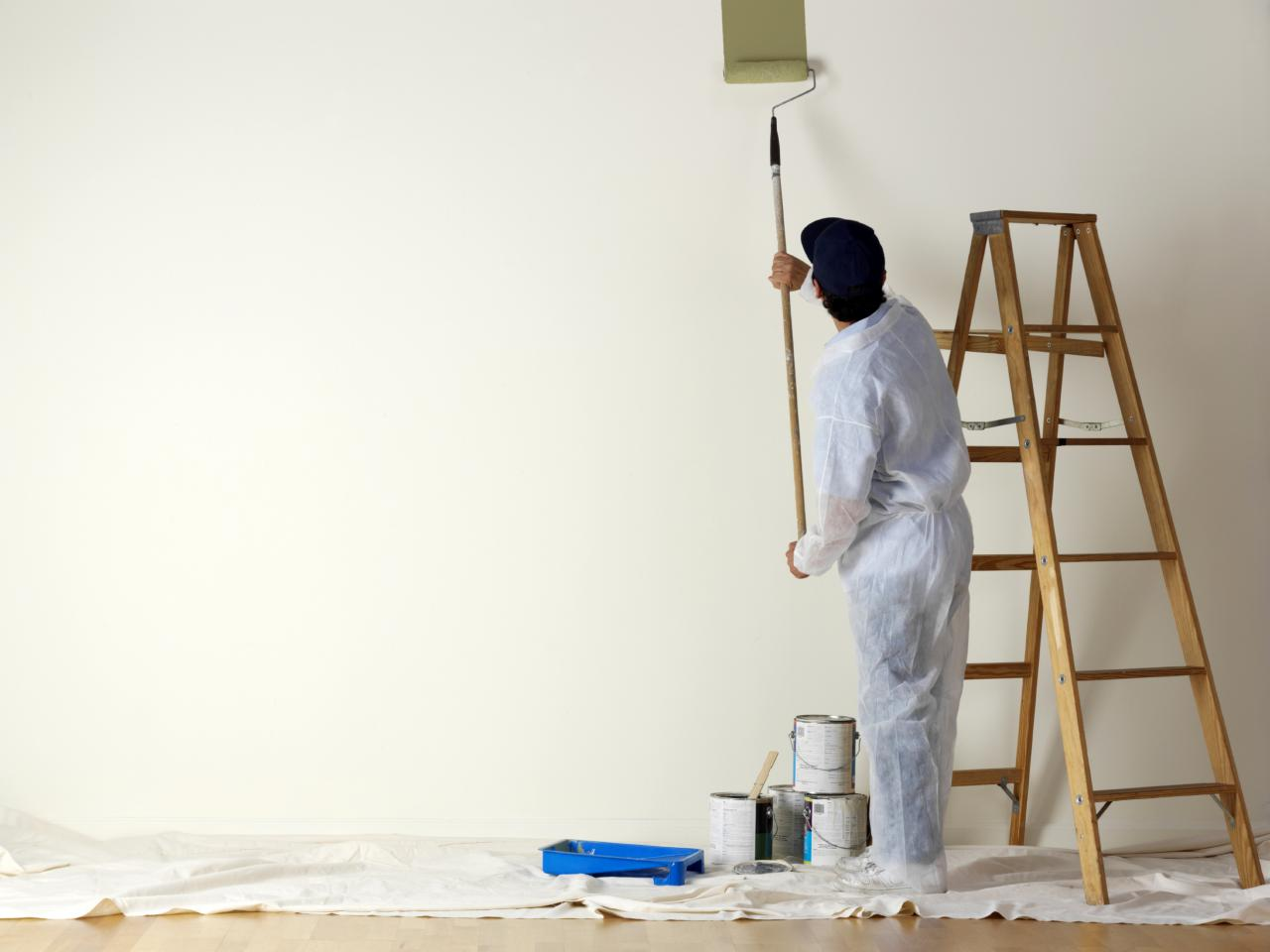 man painting a white room beige with a roller extension poll