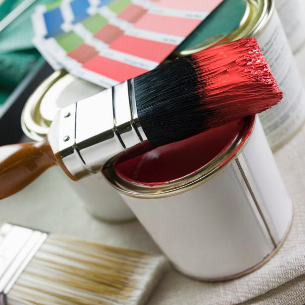 a paint brush that has been dipped in red paint sits on top of a paint tin