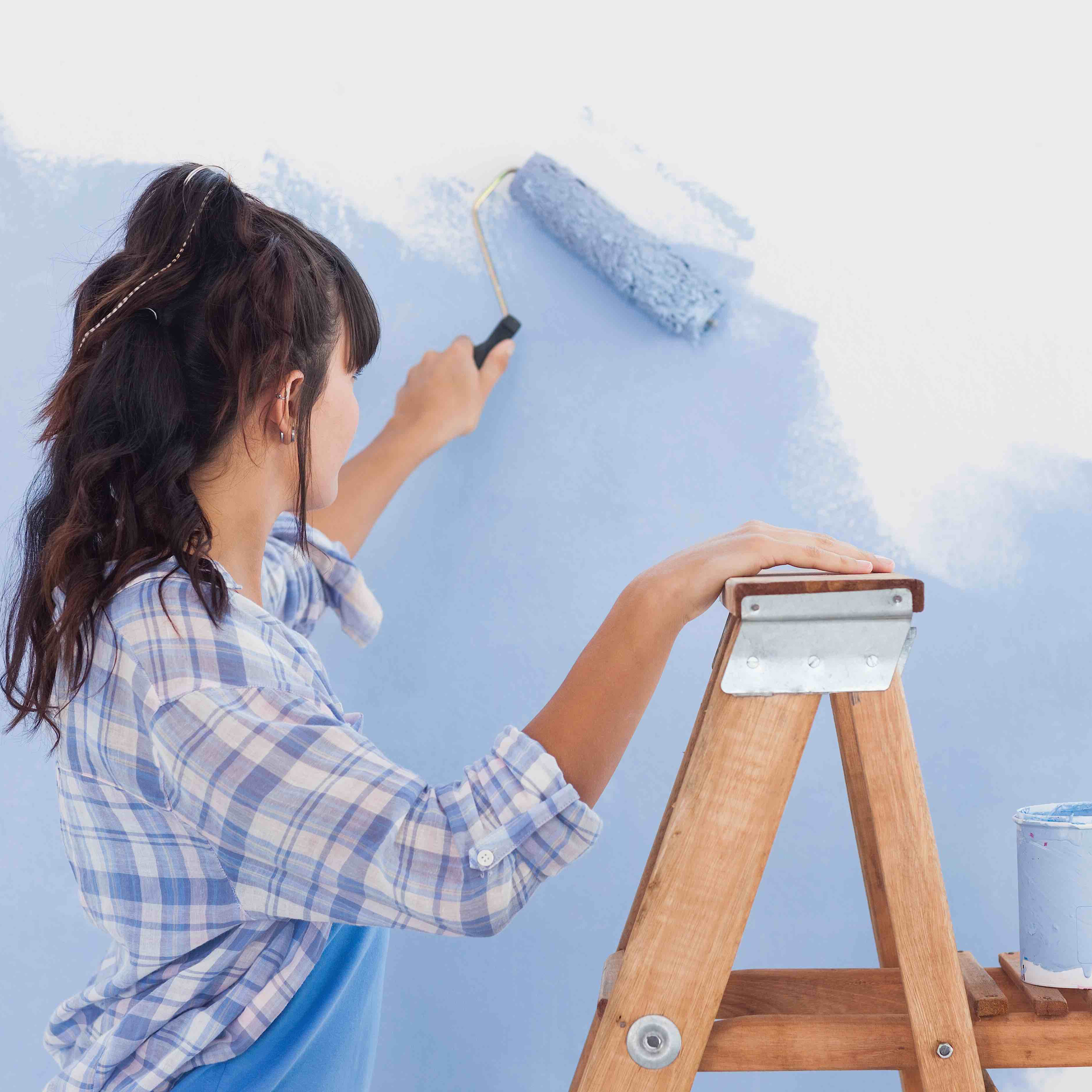 brown haired woman painting a white wall blue with a roller