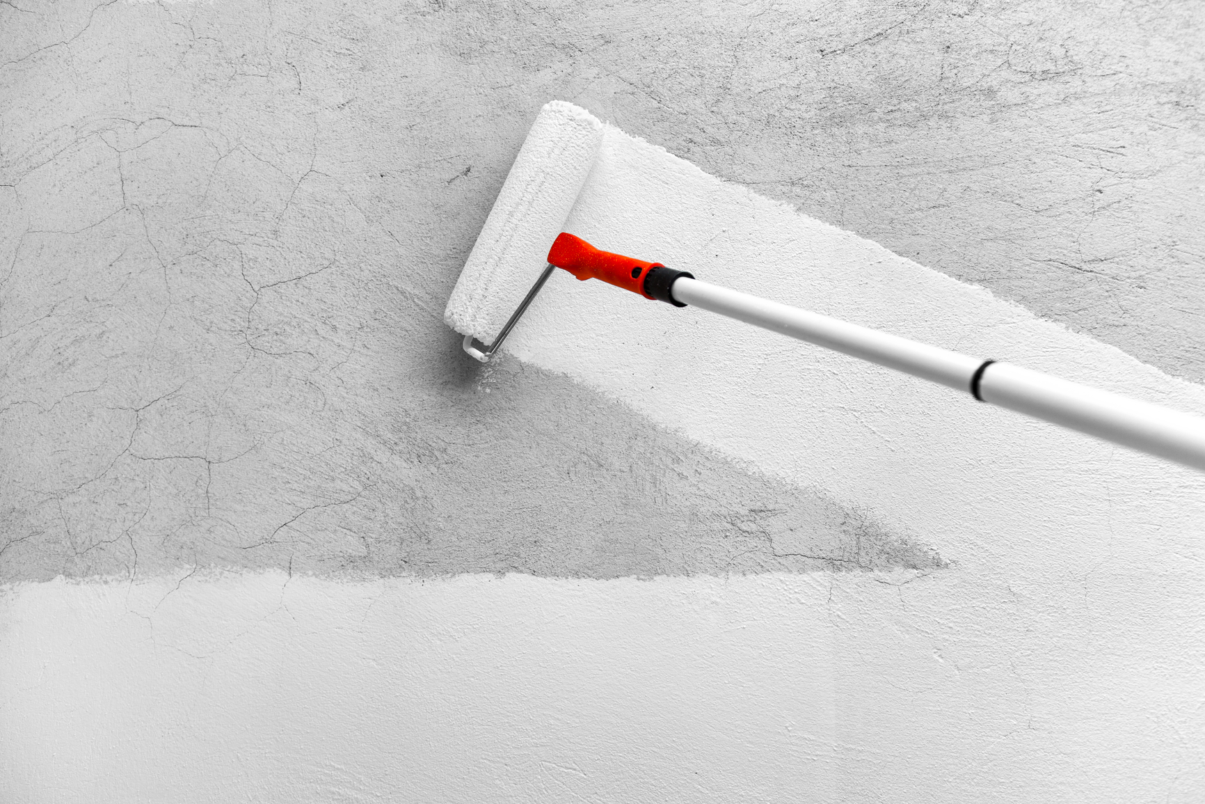 a paint roller paints a rough wall in white latex paint