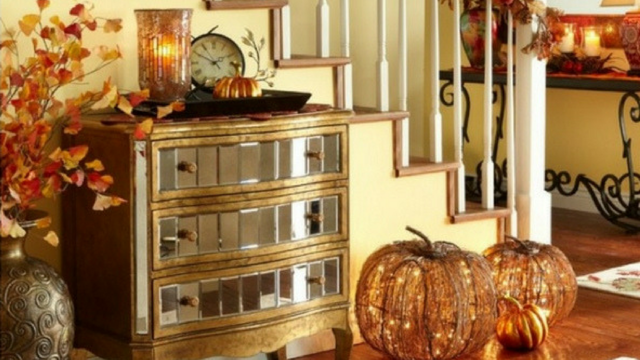 autumn decorations adorn a stairways with orange pumpkin lights, vase with leaves and a glass cabinet topped with candles