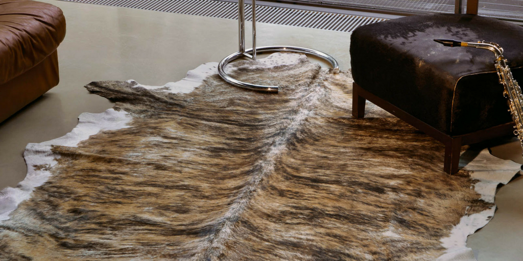 style faux fur real cowhide rug in brown and cream on a wooden floor