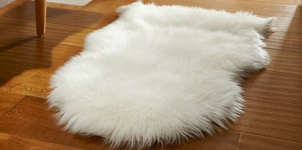sheepskin style faux fur rug on a wooden floor