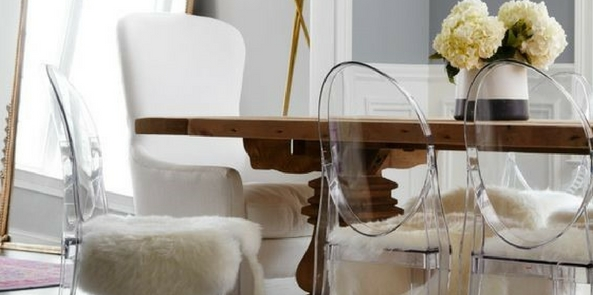 glamorous style faux fur draped over clear chairs around a wooden table with flowers on top near a large mirror