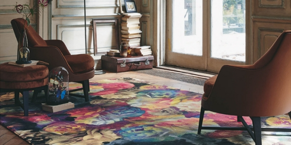 ted baker living room rug in a dark floral on a dark wooden floor with dark brown chairs on top next to a brightly lit window