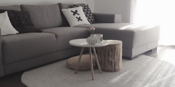a circular living room rug under a grey sofa next to a shaded window