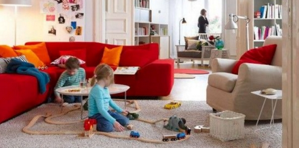 kids playing on living room rug with a trainset on a pale rug next to a bright red sofa with the kitchen in the background