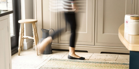 best kitchen rugs with a woman walking over a flatweave rug in a brightly lit room