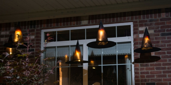 diy halloween decorations of floating witches hat hung on the front of a house with candle lights inside