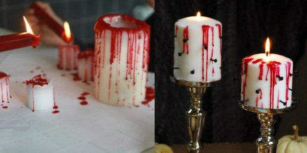 diy halloween decorations of white candles with blood wax dripping down the sides on a table with nails stuck into them