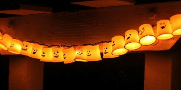 DIY halloween decorations of plastic cups with creepy faces attached to string lights
