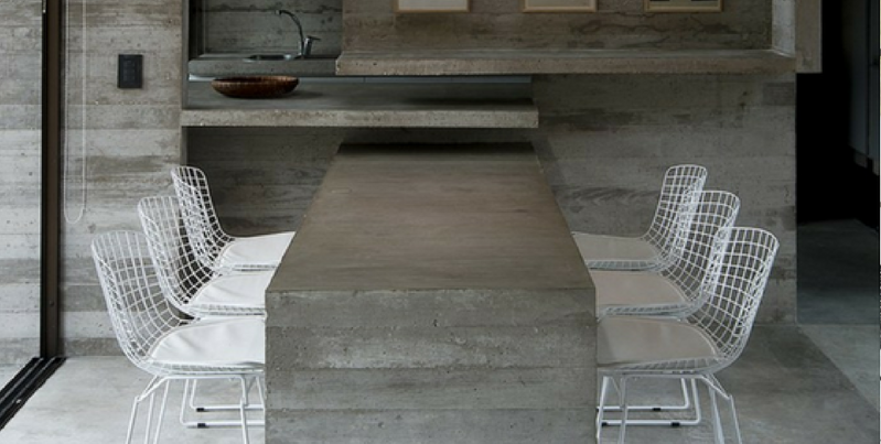 concrete furniture a concrete dining table surrounded by six white chairs