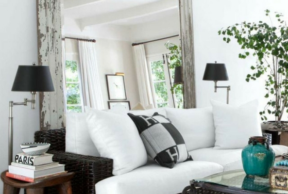 a small space using a large mirror in a living room space with white sofas
