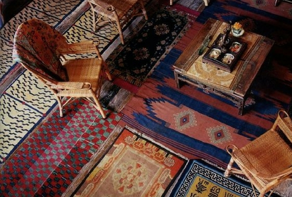 an aerial shot of layering rugs under a wooden table and wicker chairs with lots of brightly coloured traditional flatweave rugs