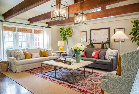 layered rugs in a brightly lit living room with wooden beams and bright bold furntiure