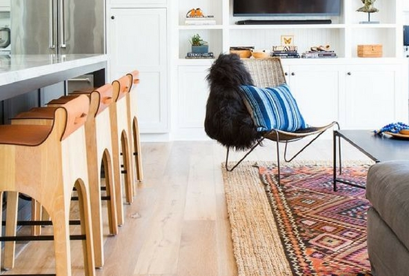 room layering rugs on top of wooden floor in a kitchen/living room to divide the space