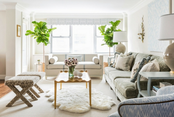 layering rugs using white sheepskin on a larger rug with leopard print stools and green and neutral shade sofas in a bright living room