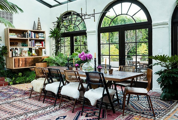 a brightly lit room with a wooden table above layering rugs in a traditional style