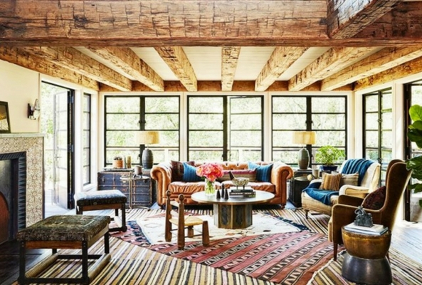 a living room with big windows and wooden beams uses bold layering rugs to create a rustic look