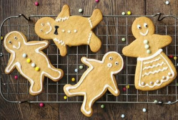 gingerbread men on a cooling tray decorated with white icing to help a room smell like christmas