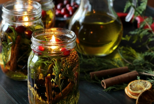 an olive oil candle filled with pine branches and berries to help a room smell like christmas