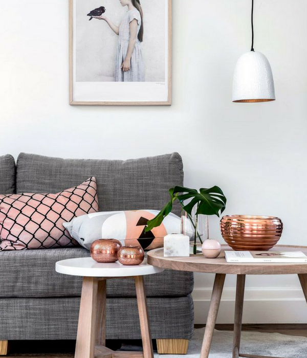 blush pink living room with a pink cushion and copper accessories