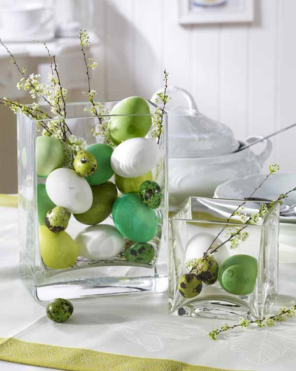 Glass vase filled with decorated eggs and twigs