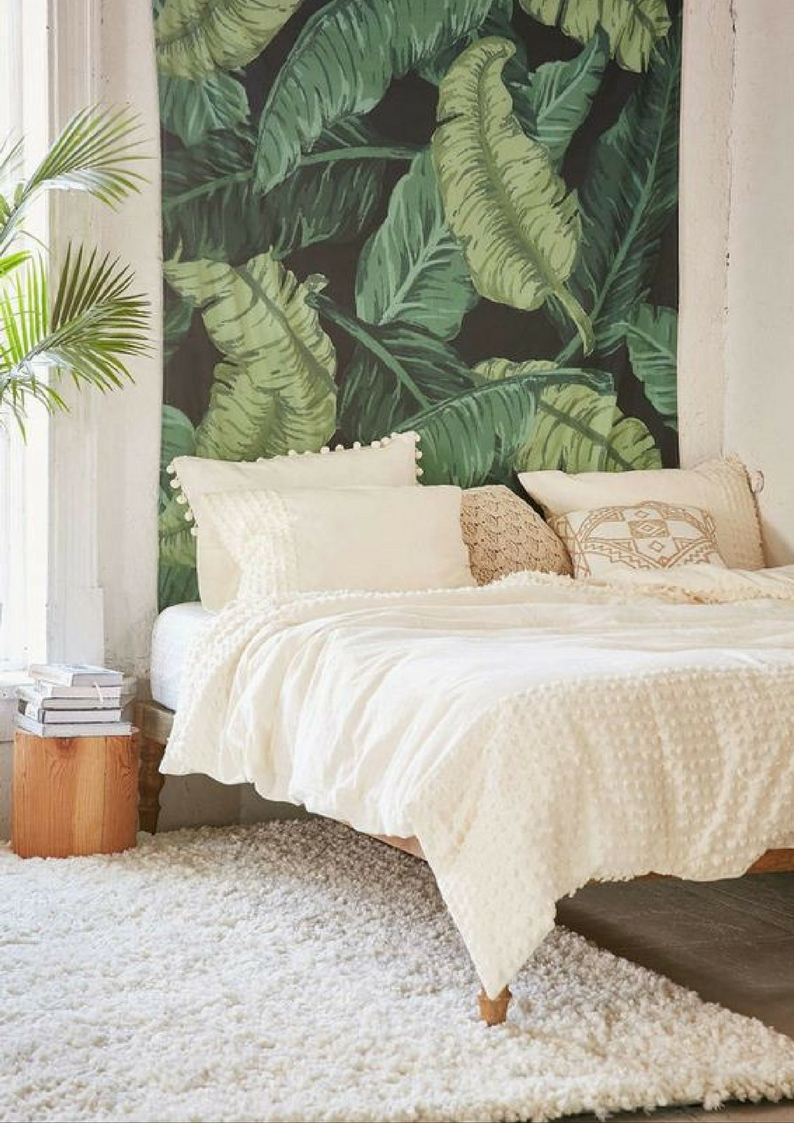 a bedroom with a botanical feature wall