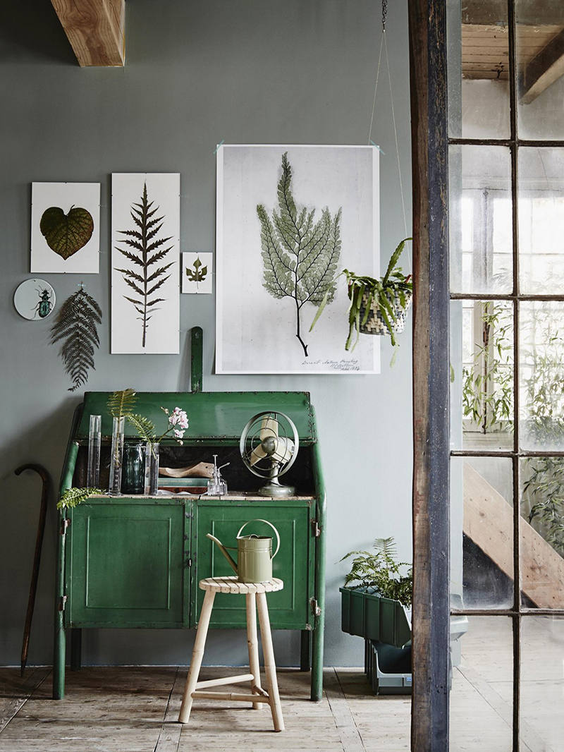 a green coloured room with a green cabinet and leafy wall art