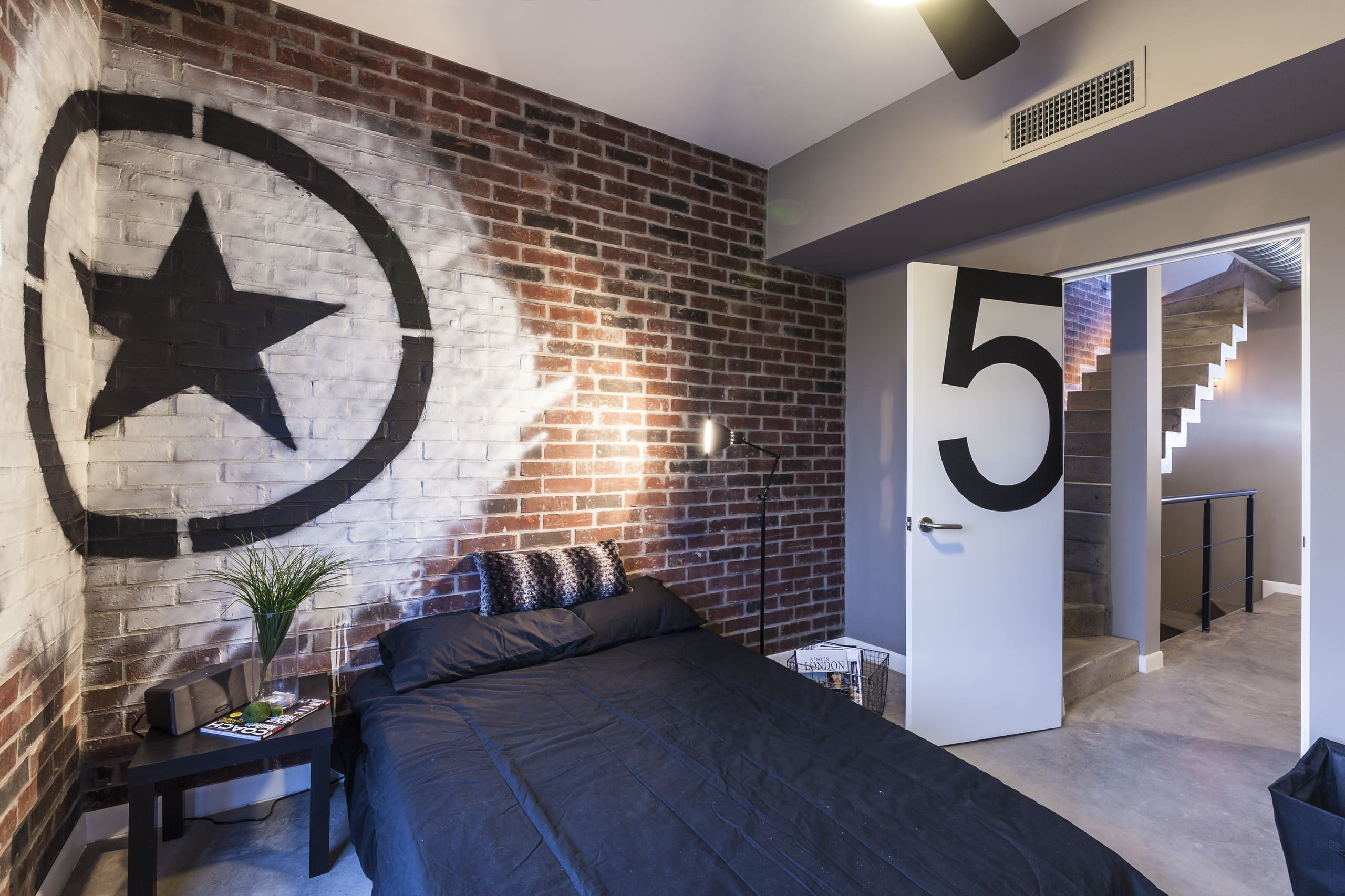 Industrial Style Bedroom With White Artwork On Exposed Brick