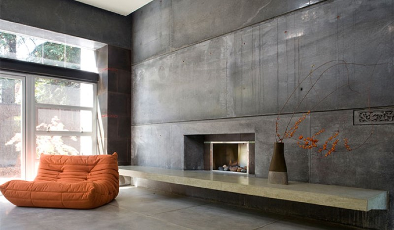 concrete interior with concrete accent wall fireplace and orange sofa - Industrial Interior Design